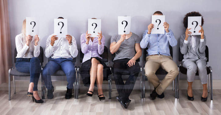 6 diverse people sitting on chairs. They are all holding up sheets with a large question mark on it, obscuring their face.