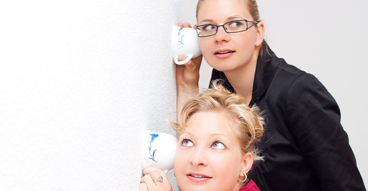 Two women listening against a wall using teacups.