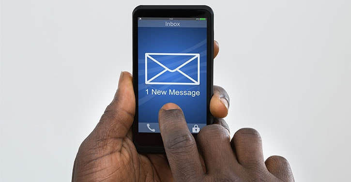 Man holding a phone with a '1 new message' and email icon on the phone that he is about to click.