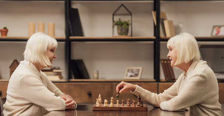 Two older women who look like twins with white hair cut into a sharp bob face off over a chess board.